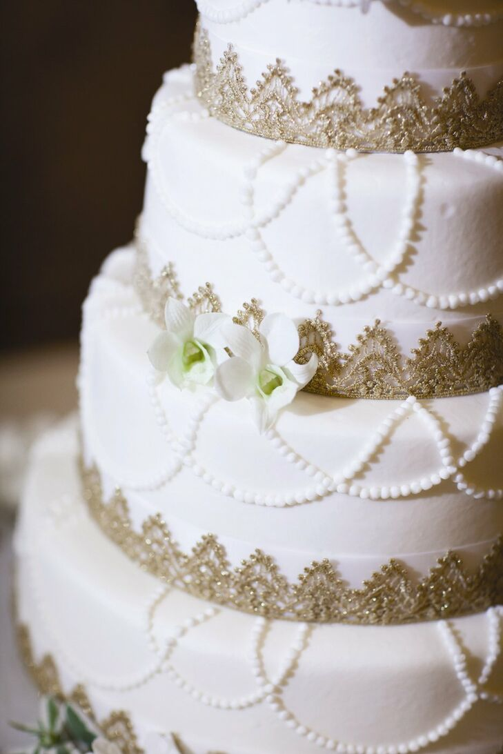 The four-tier, ivory wedding cake was decorated with hand-piped beading and gold lace at the base of each tier.