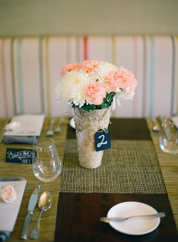 The centerpieces did double duty as table numbers: Small tags were tied to birch vases that held fluffy arrangements of pink carnations and white mums.