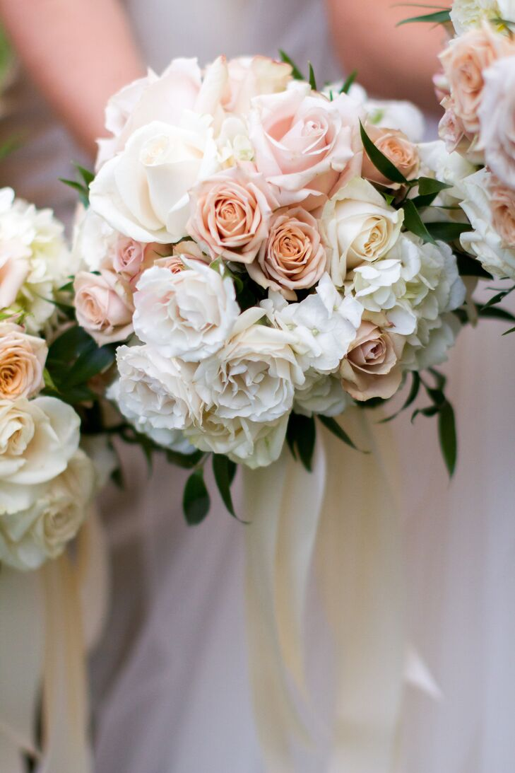 Emily's bridesmaids carried smaller versions of her own rose bouquet wrapped in an ivory satin ribbon.