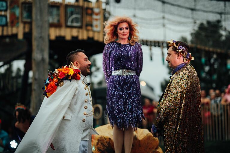 LGBTQ+ couple exchanging vows with drag queen as officiant