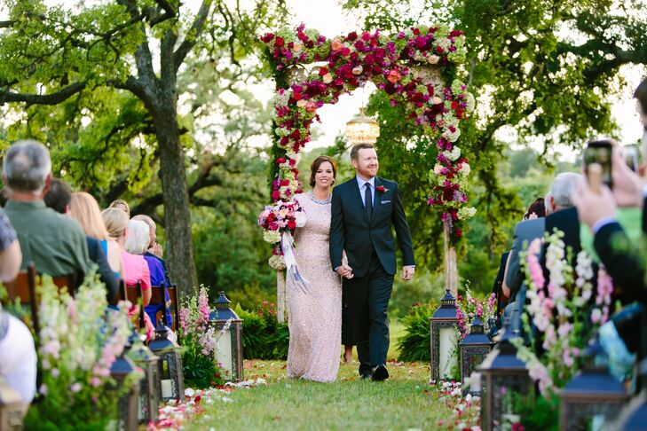 "Paige and Matt went all out for their ceremony flowers. They said ""I do"" under a wedding arch covered in bold and bright pink blooms. Lanterns, pink and white flowers and flower petals lined the grass aisle."