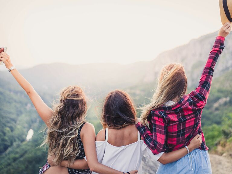 three girl friends on top of a mountain