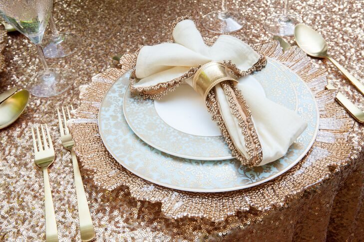 At the sweetheart table, elegant china sat on top of large gold plates. Ivory napkins trimmed with gold beading sat on top of the display, matching the gold shimmering tablecloth.