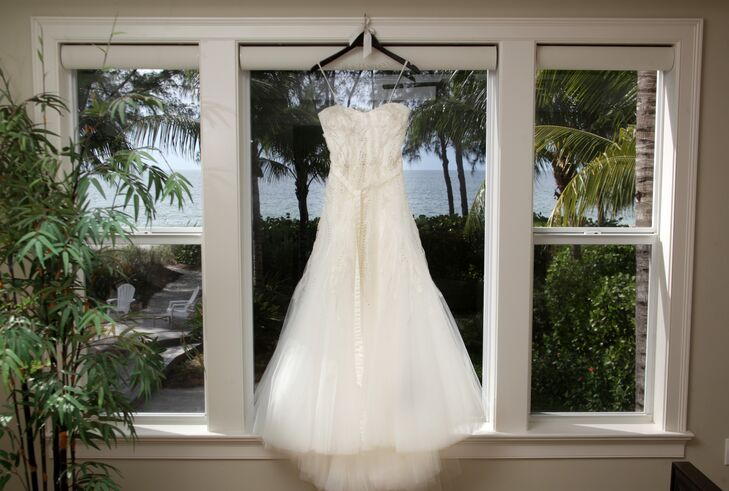 """""""I wanted to wear something that looked and felt natural, like it belonged on the beach,"""" says Elle. She wore an ivory Monique Lhuillier wedding dress with tulle, beading and embroidery."""