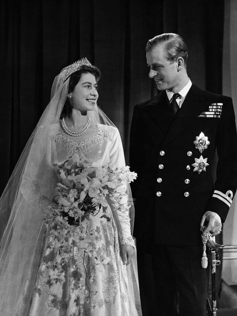 Queen Elizabeth and Prince Phillip wedding portrait showing off wedding dress and flower bouquet