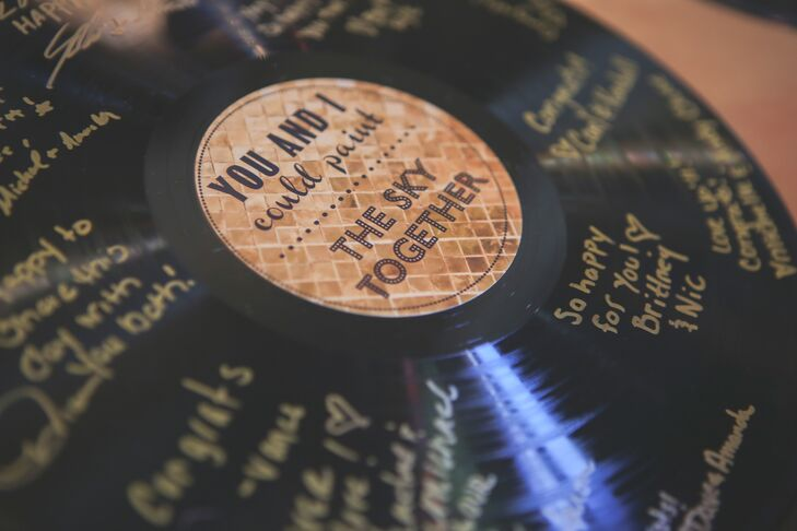 Guests left messages to the newlyweds on black vinyl records with custom gold labels.