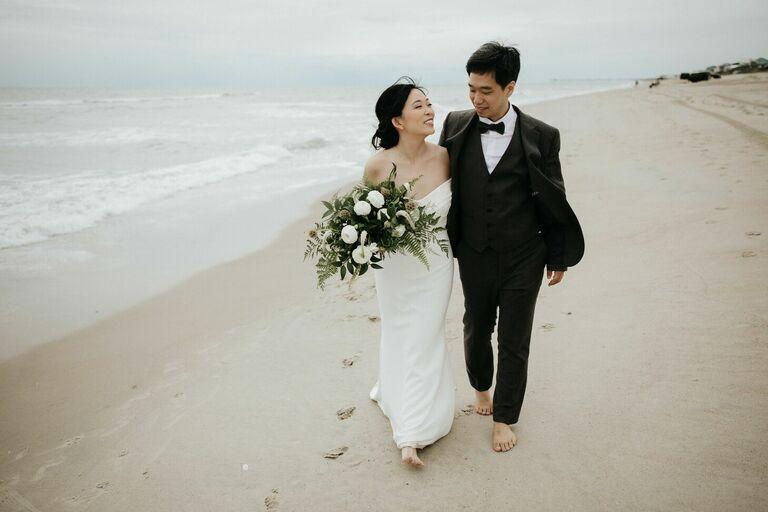 Couple walking down the beach in formal wedding attire