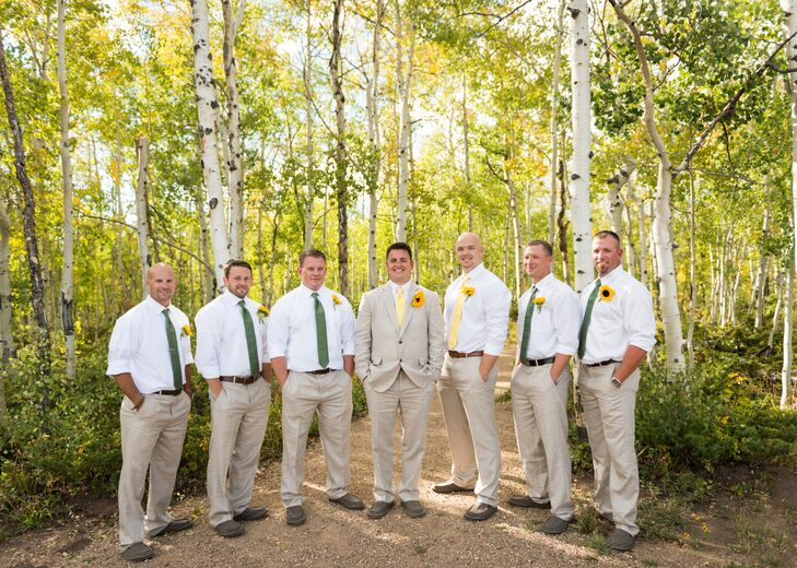 The groomsmen wore khaki pants with white shirts. The best man wore a yellow tie and the groomsmen wore green ties to match the bridesmaid dresses. They all completed the look with a sunflower boutonniere.