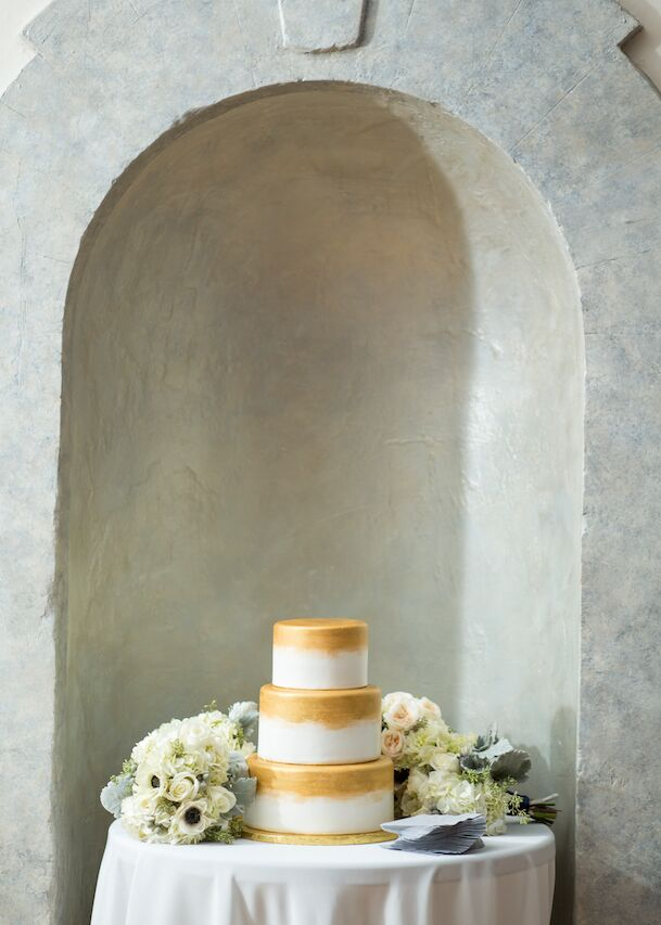 """""""We wanted something architectural and modern for the cake to contrast some of the more classic elements of the day, and we fell in love with the painted-gold design we found on Pinterest,"""" the couple says. """"The cake was a classic vanilla or champagne."""""""