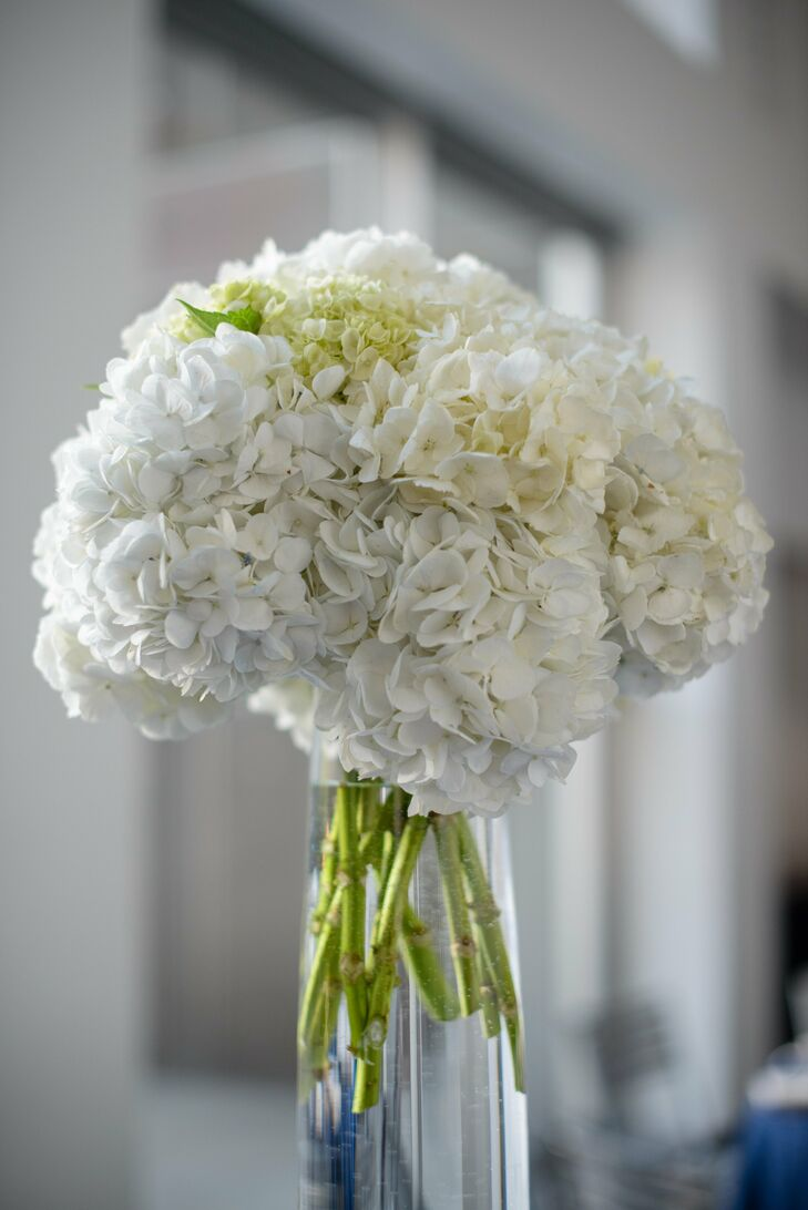 With a color palette of navy, white, beige and an earthy green, the high centerpieces of white hydrangeas brought the reception decor together perfectly. Visible through tall glass vases, the naturally green stems paired with the pure white petals of the hydrangeas contrasted beautifully against the navy table linens.