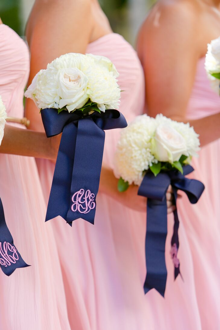 For the bridesmaids bouquets, they left the entire design up to Signature Florals. Each one was filled with off-white roses and white peonies for a timeless look. But what made the bouquets extra special were the wraps. Navy bows brought every stem together and included this chic pink monogram so every bridesmaid knew exactly which white bouquet belonged to whom.