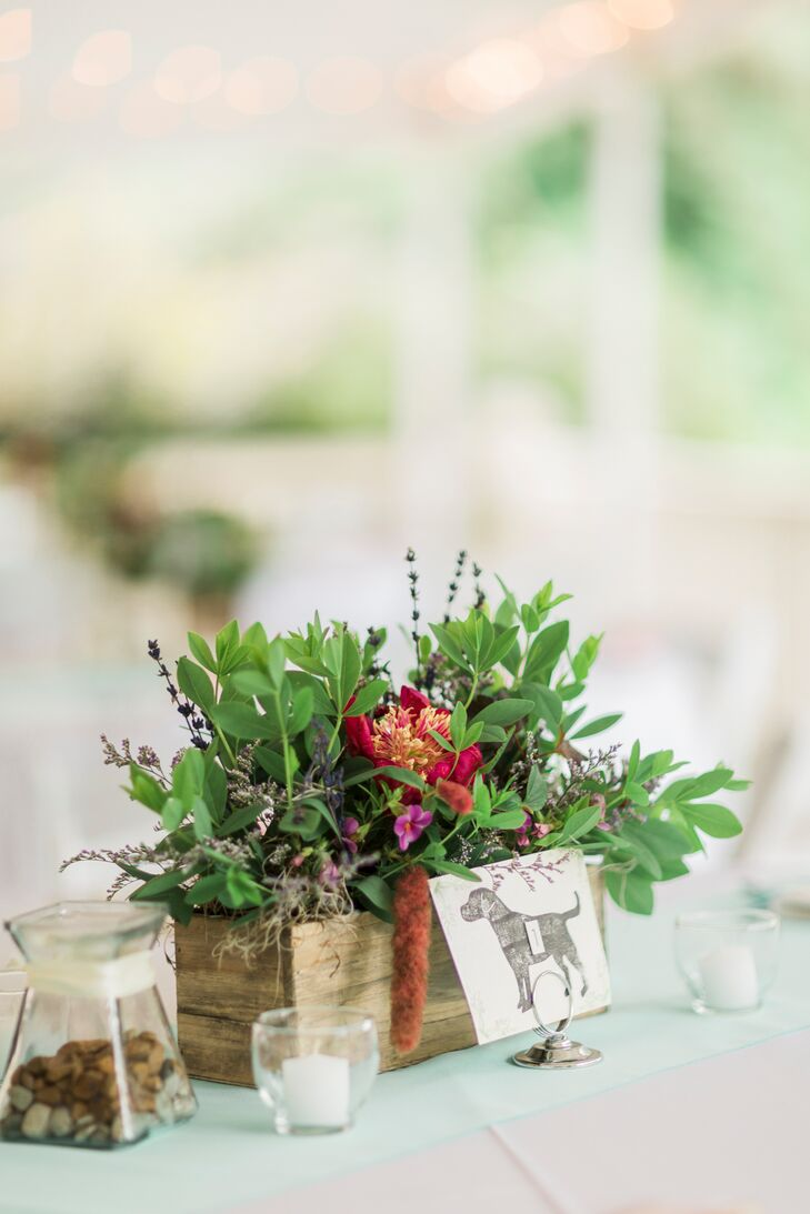 Centerpieces at the reception were made up of wooden boxes filled with greenery, bright red flowers and wildflowers. The tables were numbered with placards that featured etched dog-silhouettes.