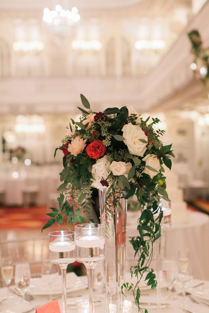 This tall centerpiece arrangement had pink and red roses along with cascading eucalyptus leaves down the side of the clear, cylindrical vase.