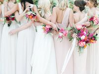 A bride embraces her bridesmaids