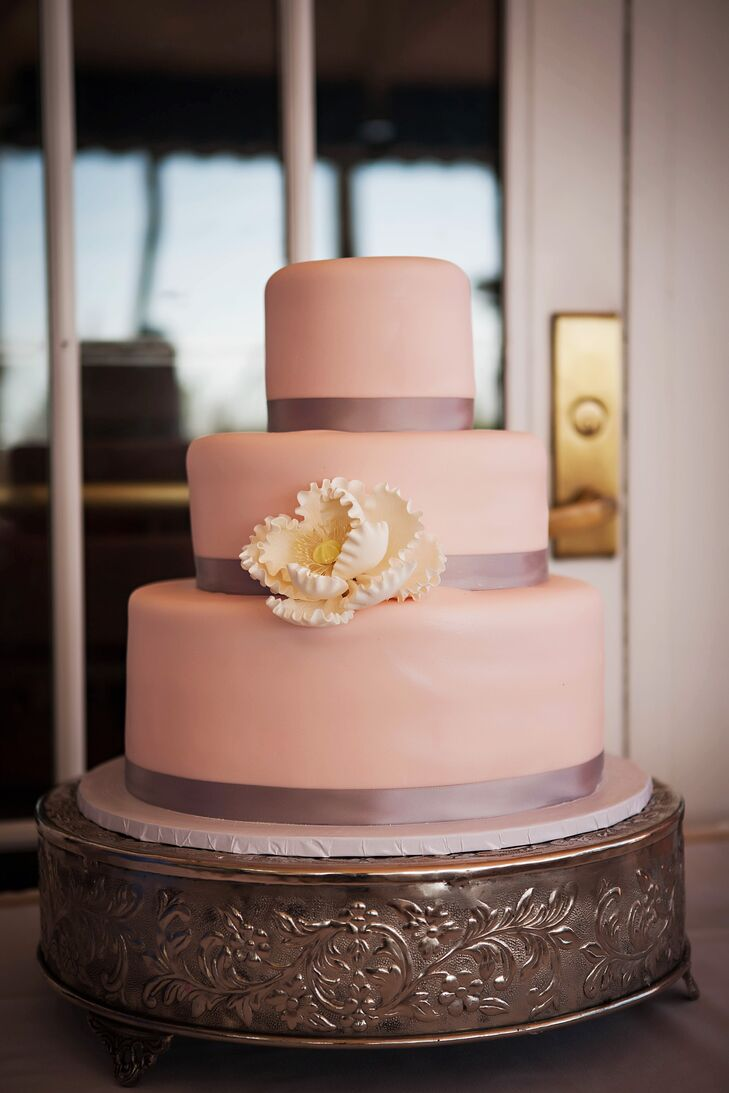 Sam and Kelly's pink Cakes by Nomeda confection matched their reception and ceremony location. Their other hues were also brought into the mix with a large white flower and a navy ribbon on each tier.
