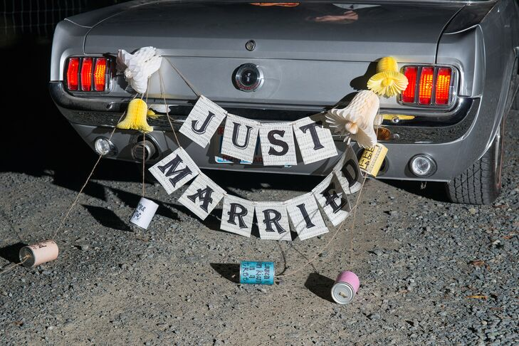"""The newlyweds drove off in a vintage convertible decorated with a retro """"Just Married"""" banner complete with tin cans."""