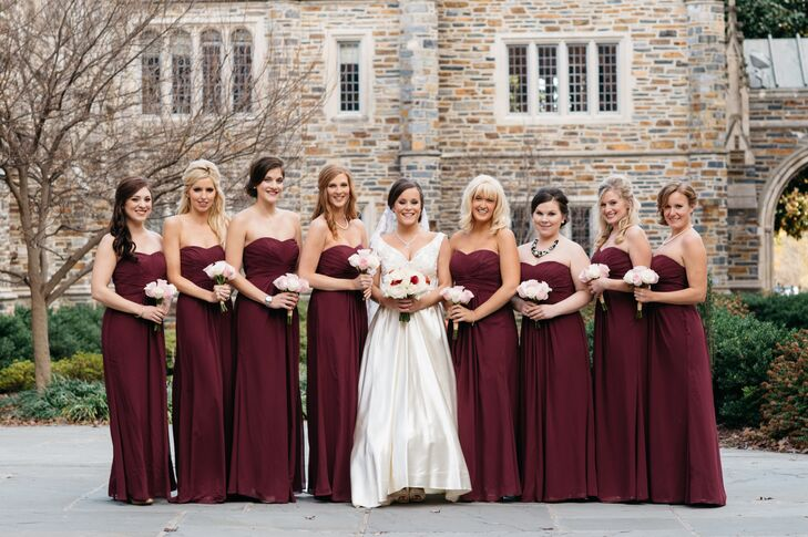 The bridesmaids wore strapless burgundy dresses for the November wedding. Kara and Pat wanted the wedding to suit the late fall season, with a pop of dark color. They added whatever jewelry they wanted and blush and ivory rose bouquets.