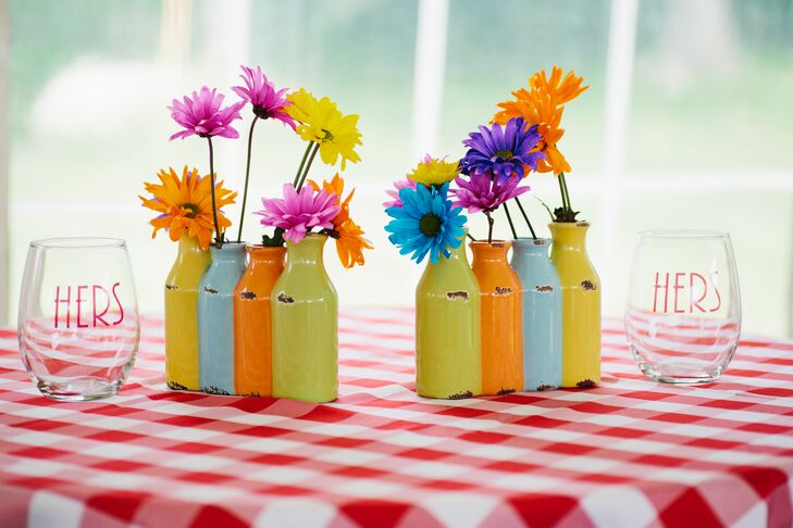 "Colorful glass bottles held Gerbera daisies that the couple got from the grocery store. ""We wanted the flowers on the table to look unplanned,"" says Katrina. The red gingham table clothes were sewn by Katrina's aunt."