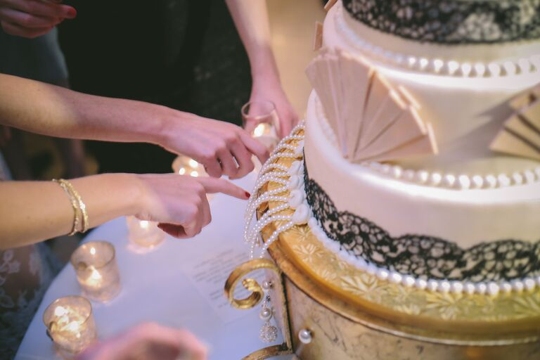 Women pulling charms from a wedding cake