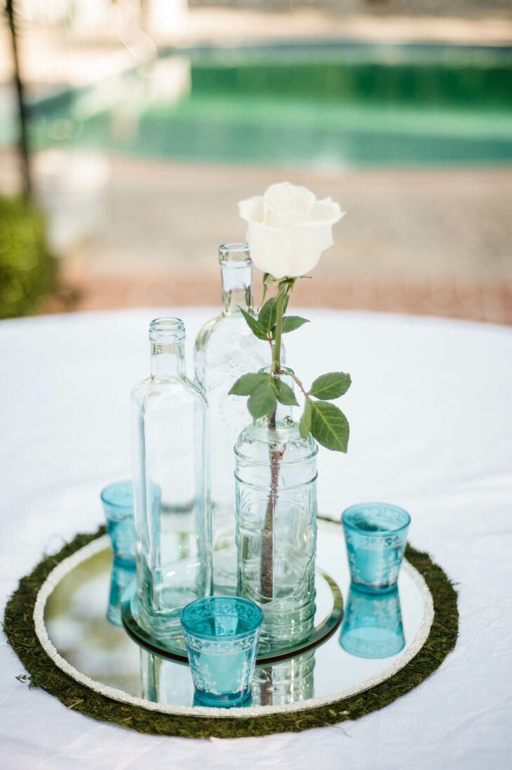 Each table was decorated with an arrangement of antique aqua glass bottles on moss placemats.