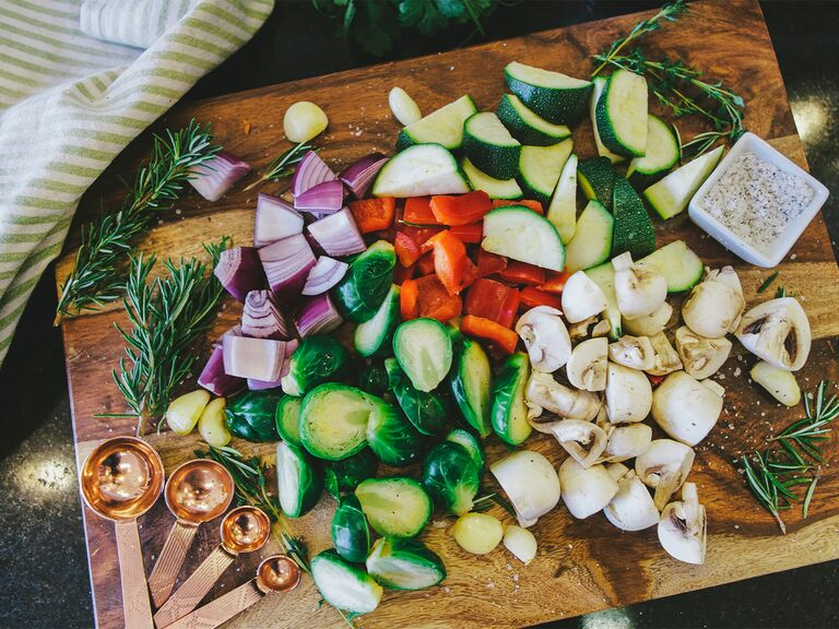 Cut up vegetables and herbs on wooden cutting board