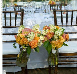 Mason jars filled with dahlias, roses and stock hung from the  bride and groom's chairs.