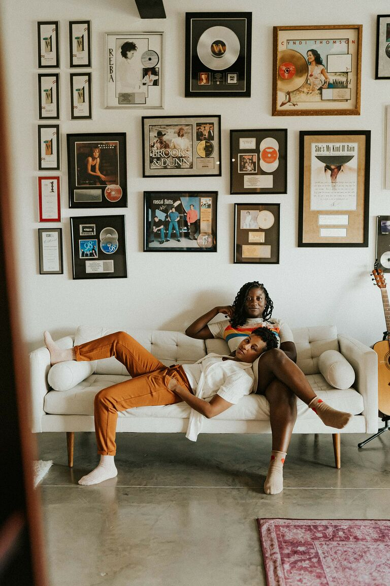 Same-sex couple relaxes on couch surrounded by vinyl records