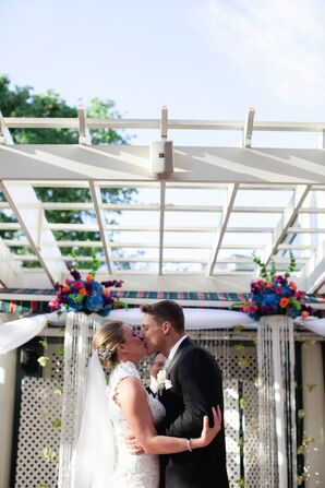 First Kiss Under White Pergola with Colorful Flower Arrangements