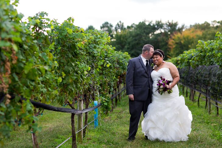 Veronica and John leaned toward one another as they stood next to the vineyards at Williamsburg Winery.