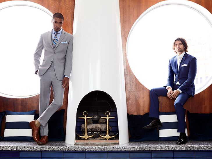 groomsman in gray suit and groom in navy suit