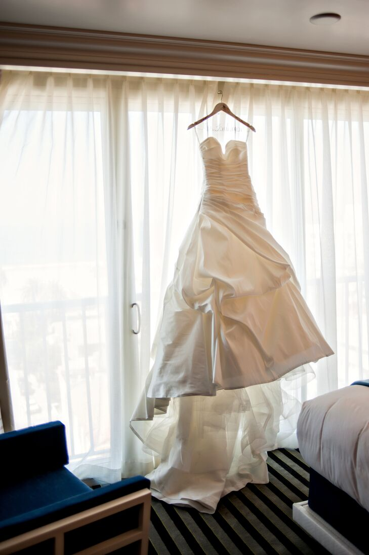 The bride wanted a simple sweetheart ball gown without a lot of embellishment but a lot of volume. She wore a white satin ball gown by Enzoani with gathered details and a train.