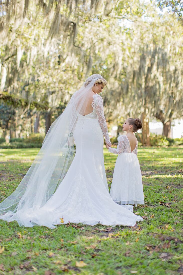 The flower girl's dress resembled the bride's gown with long lace sleeves and a low back.