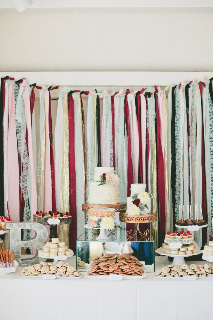 The dessert buffet table was fully stocked with a number of cakes, cupcakes and cookies. Colorful strands of streaming fabric served as a backdrop.