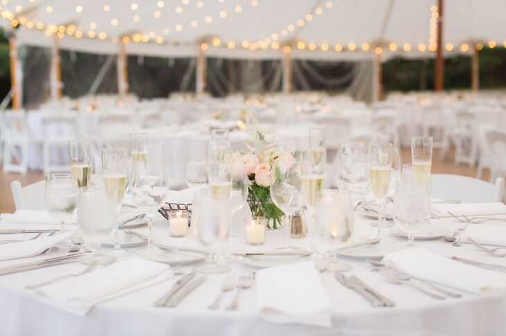 The couple chose simple, minimal decor of white linens, tealights, and small centerpiece arrangements of pink roses for their tented outdoor reception at the Estate at Moraine Farm in Beverly, Massachusetts.