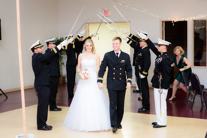 """""""A special military tradition, which occurred when we were being announced as a couple, was the sword arch,"""" says the couple. """"Charles's military buddies formed two lines and crossed their swords in between. The newlyweds had to walk under an arch of these swords as they were introduced. As they approached each set of swords the officers would lower their swords, and demand, """"A Kiss to Pass"""" to much applause! At the last sword, Charles's best man swatted Micaela's bottom with the sword, and loudly announced """"WELCOME TO THE NAVY, MRS. JONES."""""""""""
