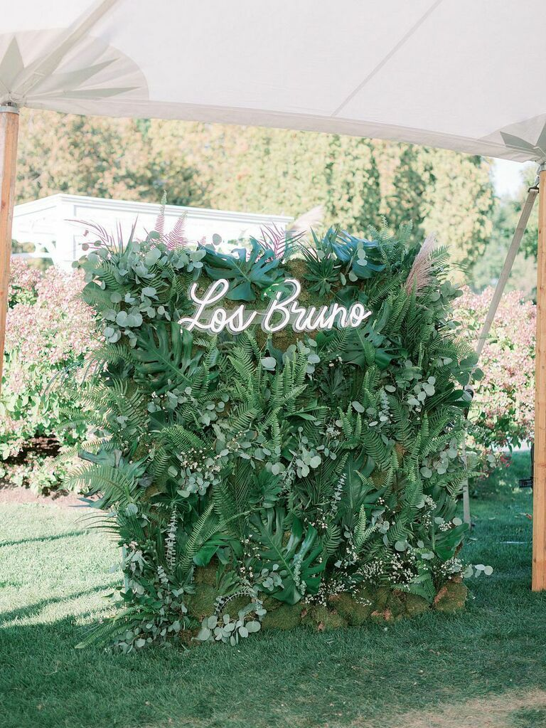 Lush wedding wall of greenery leaves and sprigs with white neon last name sign