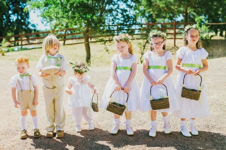 Emily's nieces served as flower girls, and each wore a lacy white dress with a green sash that tied into the natural, rustic palette. The ring bearer sported a khaki suit and suspenders, mirroring Vishal and his groomsmen.