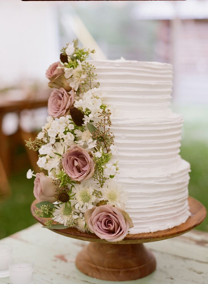 For dessert, Chutney and Steve enjoyed a three-tier white buttercream cake. It was decorated with cascading white hydrangeas, white scabiosas, seeded eucalyptus and light burgundy roses.