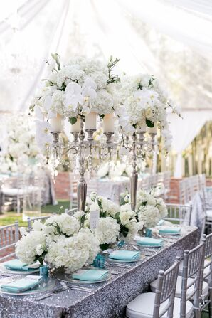 Tall Candle Centerpiece with Orchids on Silver Glitter Tablecloth