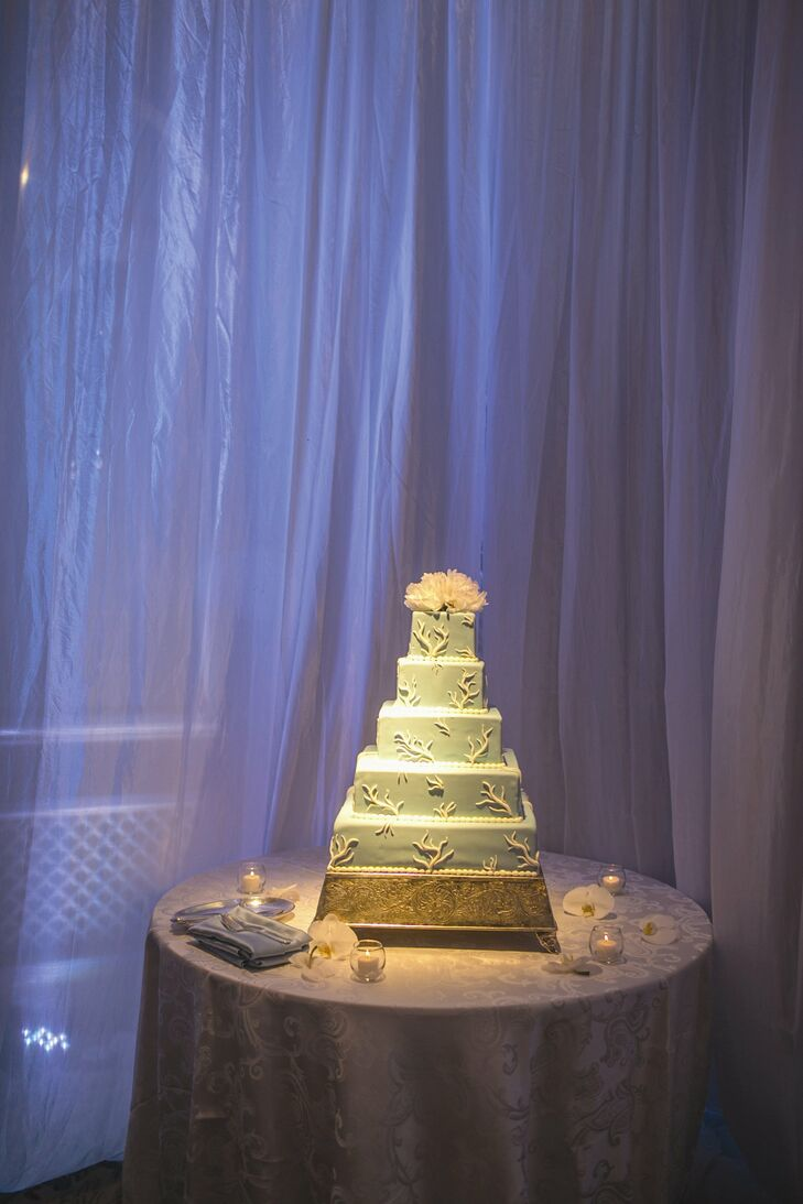 The five-tier, square wedding cake was iced in light blue fondant with a subtle white coral design. Two blush peonies topped the elegant confection.