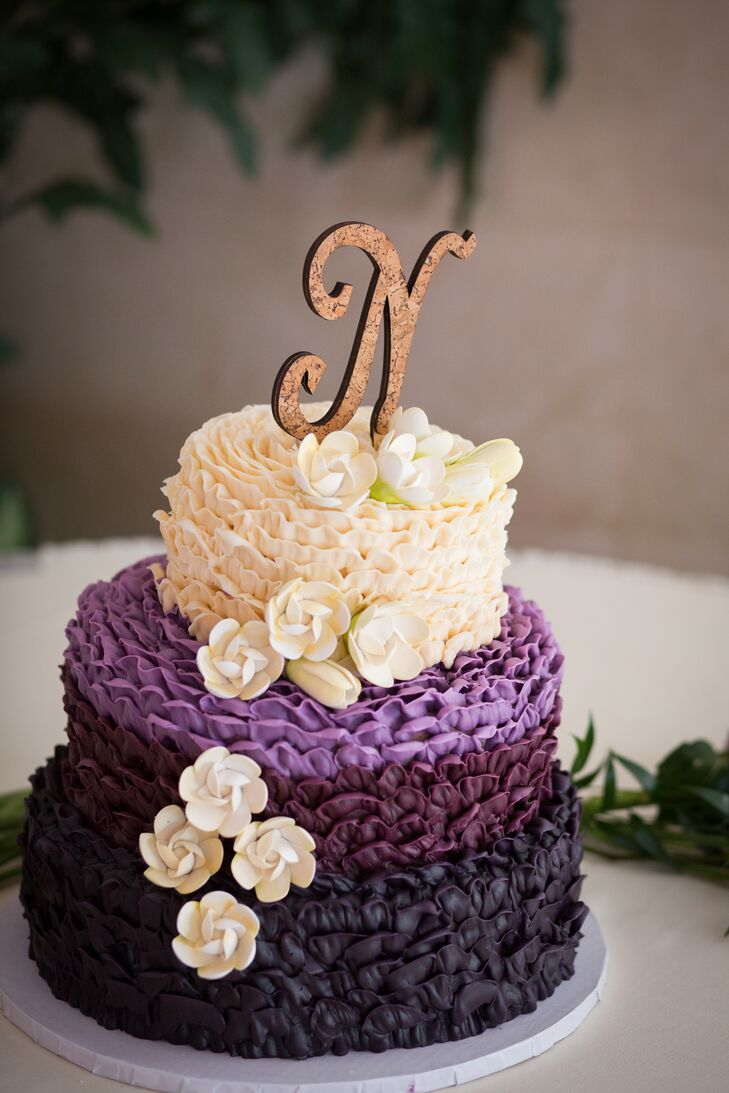 """To go along with the winery theme, the """"N"""" cake topper on the wine purple wedding cake was made from cork."""