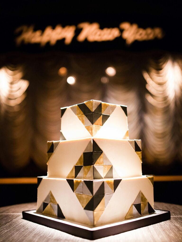 Square three-tier white wedding cake with black, gold and silver Art Deco pattern