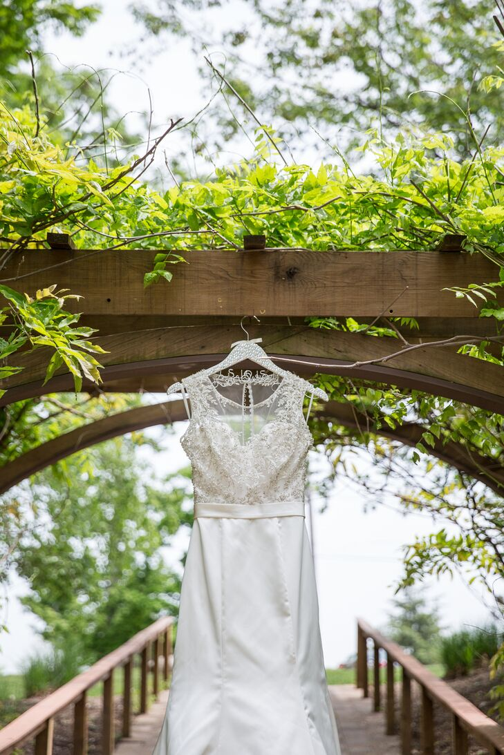 """After a long search, Lindsey finally found her dress at Bijou Bridal Boutique. For her dream gown, she had a vision of a high illusion neckline with a sweetheart cut. """"I wanted formfitting, but not without a little flare,"""" she says of the bodice's embellishment. """"I loved the idea of timeless lines with added dramatic qualities."""""""