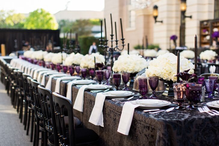 Florist R. Jack Balthazar placed white bouquets and intense purple lisianthus atop the long banquet table alongside textured mercury-glass votives and vases. Vintage silver cloches with tags attached held vintage bat masks for guests to wear throughout the night.