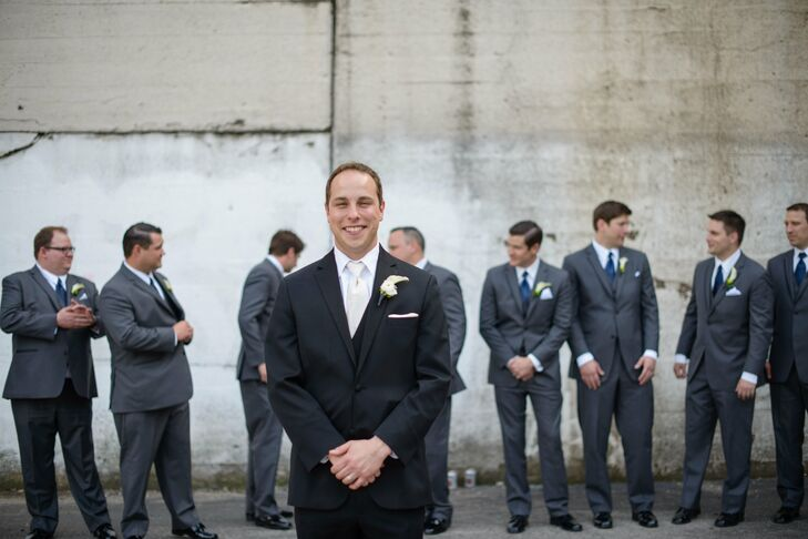 Ryan sported a Vera Wang classic black tuxedo for the wedding from Men's Wearhouse. He accessorized his outfit with a pure white tie and a ranunculus and dusty miller boutonniere. The groomsmen wore Vera Wang charcoal tuxedos with navy ties also, from Men's Wearhouse, accessorizing with matching boutonnieres and black dress shoes.