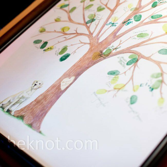"The couple commissioned a local artist to paint the tree for their thumbprint guest book. For some extra-personal touches, their yellow Lab sits next to the tree, and Alison and Scott's initials are ""carved"" into the trunk."