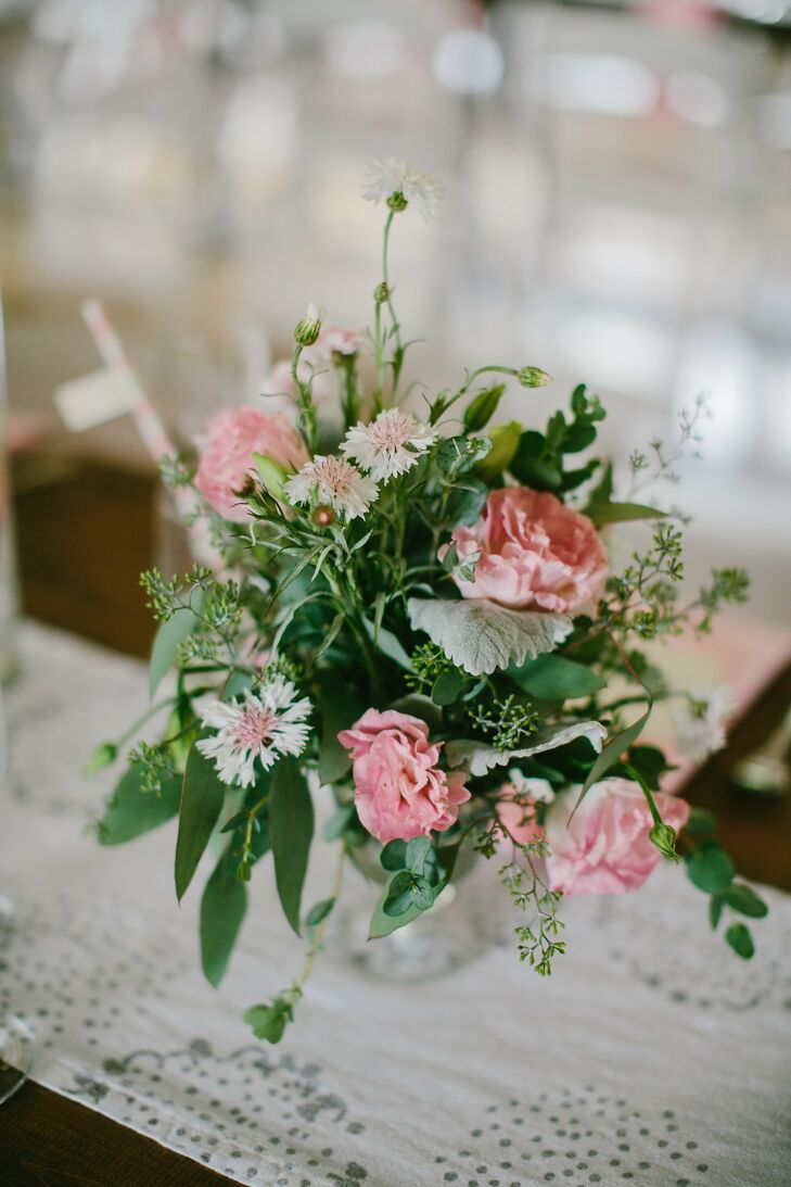 Pink roses and assorted greenery added a rustic look the the centerpiece decor.
