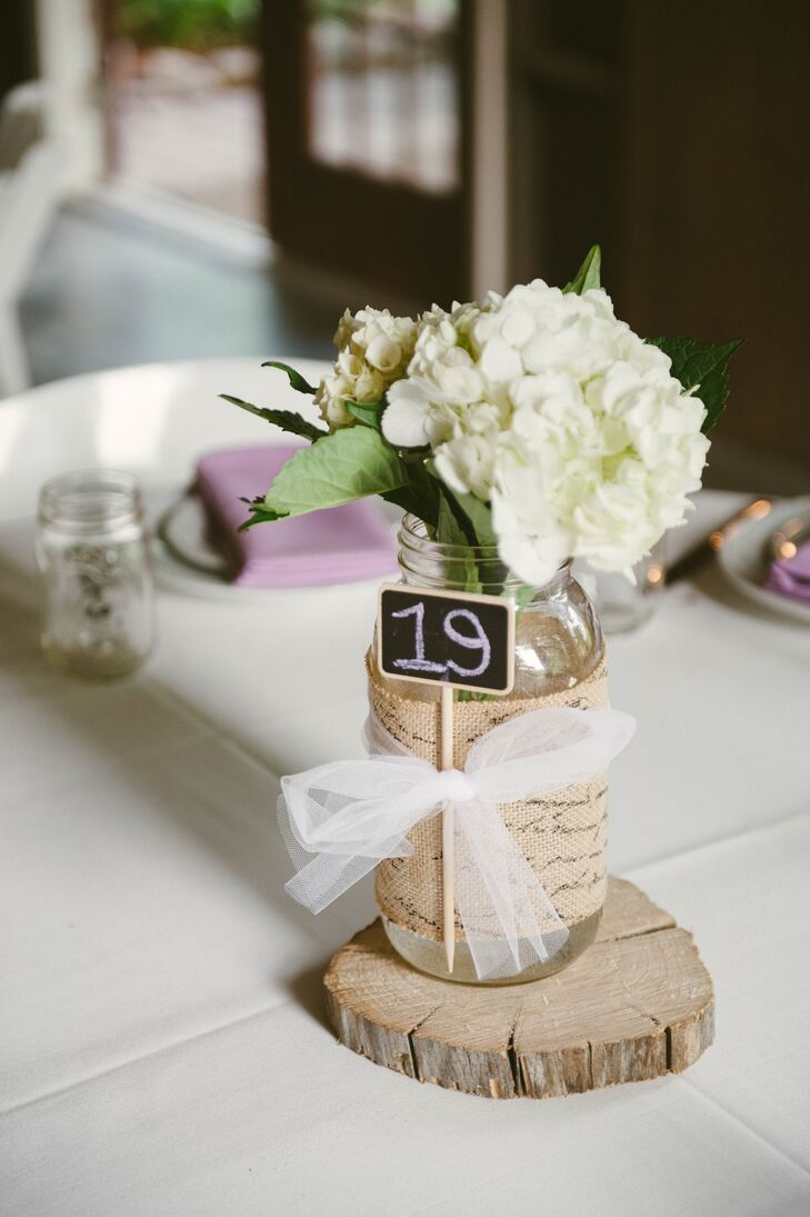 The flower girls walked down the aisle with small bouquets that later acted as centerpieces at some of the tables. Katie tied ribbons around burlap-wrapped mason jars to keep miniature chalkboard table number signs in place. Each jar sat atop a circular wooden slab, which had been cut by a family member.