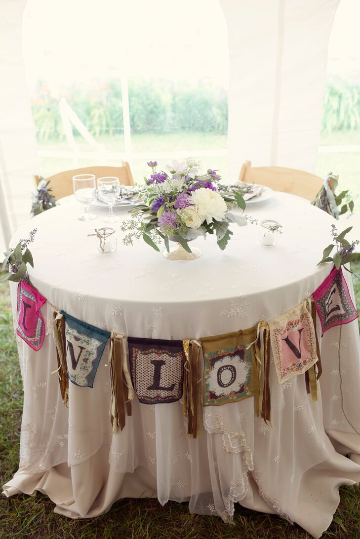 """Heather's mom handmade the bunting for the sweetheart table that read """"In Love."""" Heather and Jordan also hired their florist to create heart-shaped floral arrangements for all the place settings."""