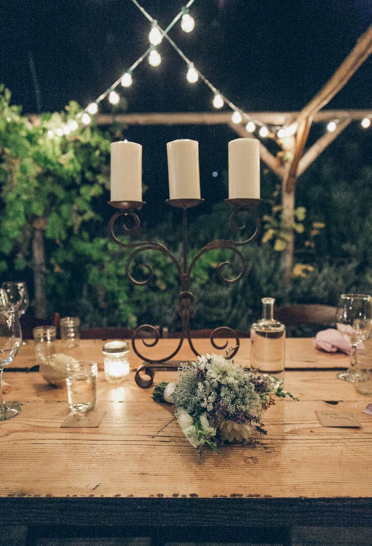 An iron candelabra holding up white candles created a romantic glow to the wooden dining table displays, decorated with various DIY accents. Guests drank out of mason jars set on the wooden surface of dining tables.
